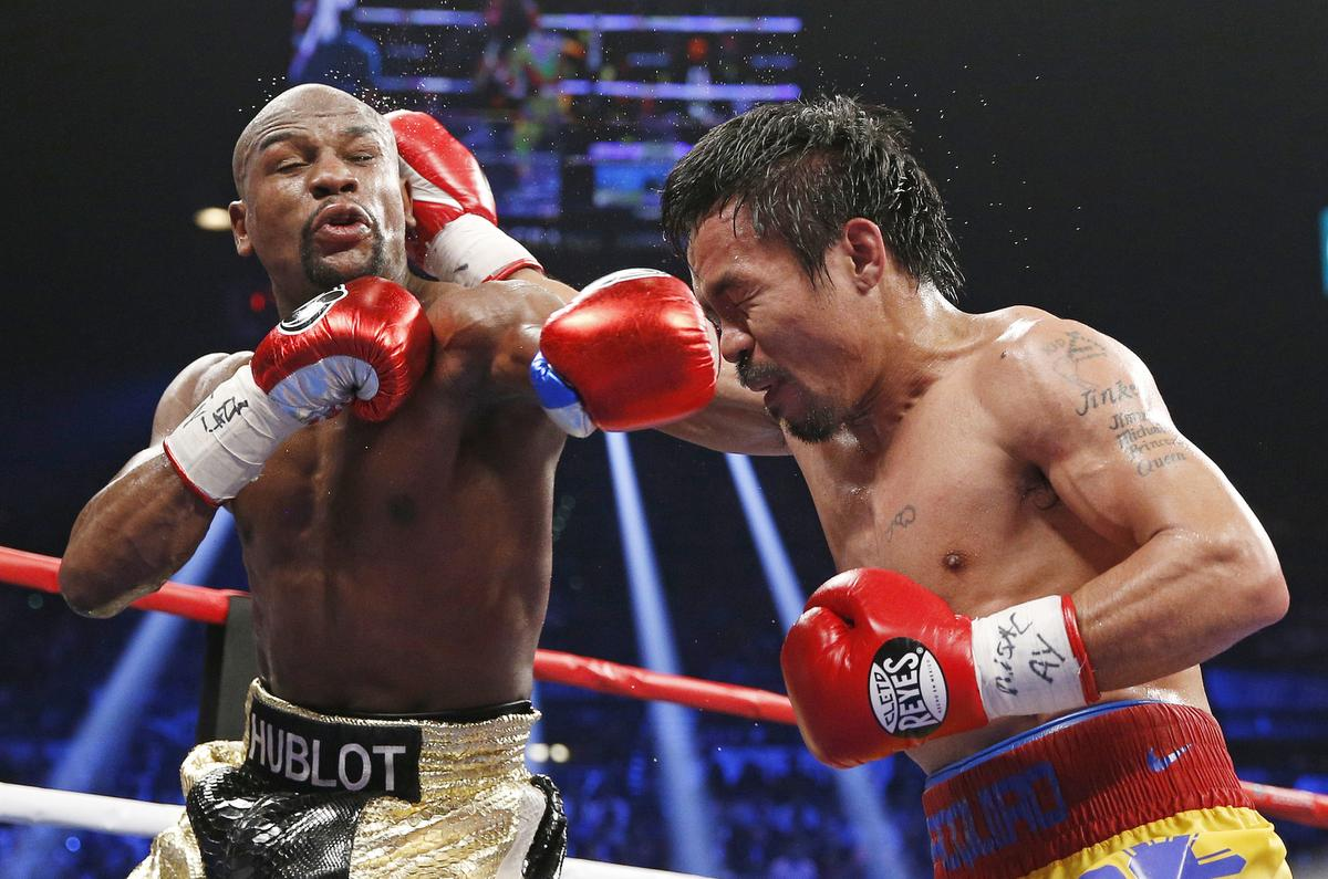 Floyd Mayweather Jr., left, faces off with Manny Pacquiao, from the Philippines, during their welterweight title fight on Saturday, May 2, 2015 in Las Vegas. (AP Photo/John Locher)